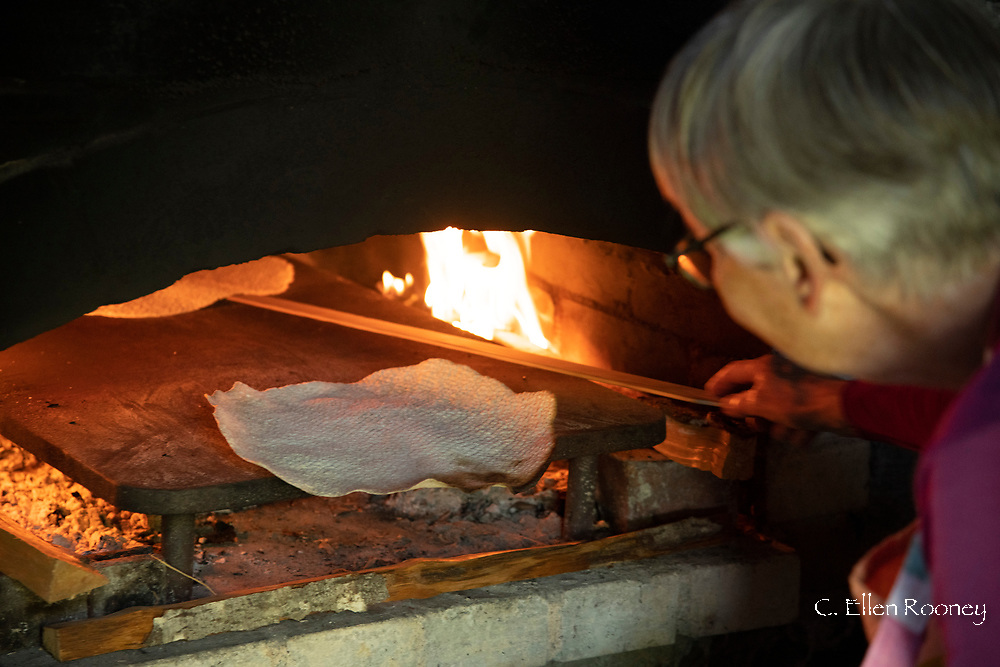 A woman baking flatbread at the Hardanger Folk Museum in Utne, Vestlandet, Norway