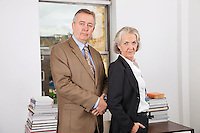 Portrait of confident businessman and woman in office