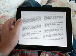 Man reading digital e-book using Amazon Kindle app on an iPad touch screen tablet computer