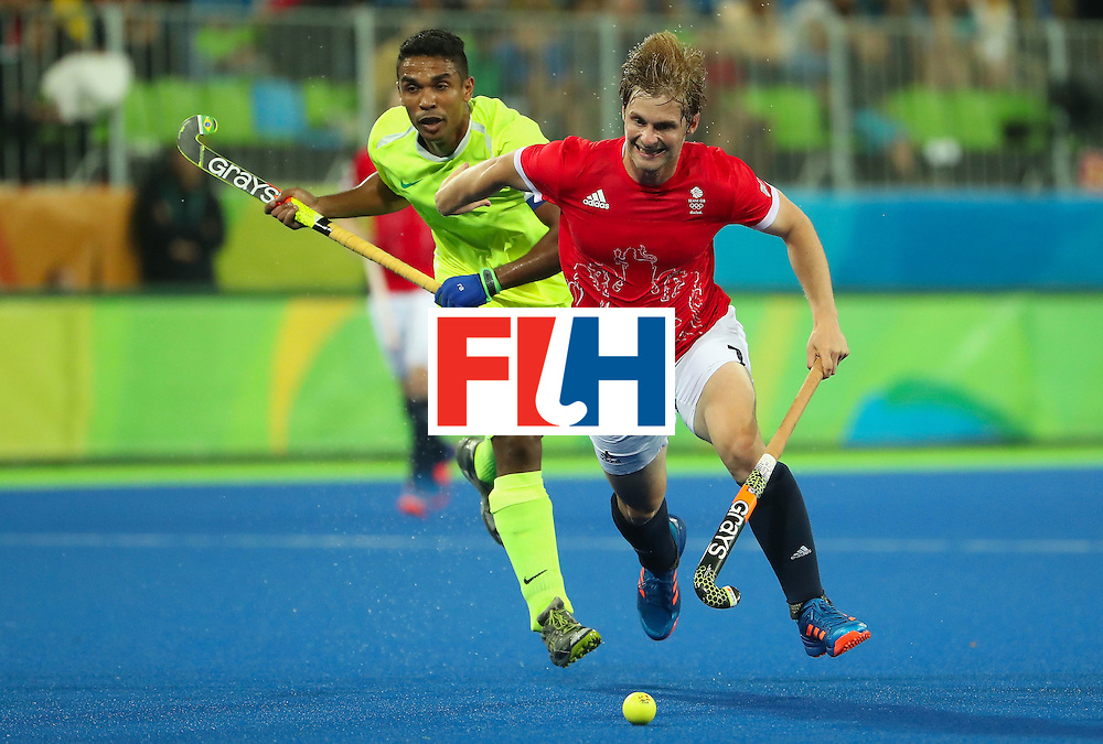 RIO DE JANEIRO, BRAZIL - AUGUST 09:  Ashley Jackson #7 of Great Britain moves the ball past Andre Patrocinio #7 of Brazil during the hockey game on Day 4 of the Rio 2016 Olympic Games at the Olympic Hockey Centre on August 9, 2016 in Rio de Janeiro, Brazil.  (Photo by Christian Petersen/Getty Images)