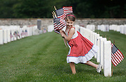 Delaney Gardner, 6, runs with a hand full of flags while helping to decorate veteran's graves on Thursday, May 26, 2016 in preparation for Memorial Day at the Springfield National Cemetery.
