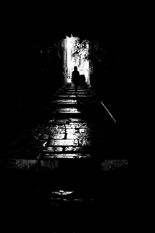 Woman in Hat walks through allyway at Night, Croatia
