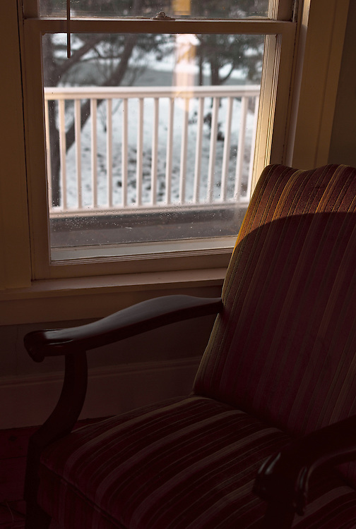 Window and empty chair in winter afternoon light