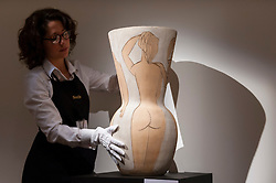 "© Licensed to London News Pictures. 18/11/2016. London, UK. A staff member examines ""Grande Vase Aux Femmes Nues"" by Pablo Picasso (est. GBP250-350k), at the preview at Sotheby's of works on view at four upcoming November auctions featuring Modern & Post-War British Art, A Painter's Paradise (Julian Trevelyan & Mary Fedden at Durham Wharf), Scottish Art and Picasso Ceramics from the Lord & Lady Attenborough Private Collection. Photo credit : Stephen Chung/LNP"