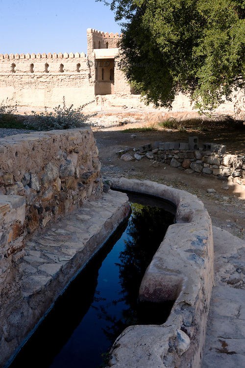 Oman, fortress at Al Rustaq, originally established by Persians, 6th century AD; closeup of a falaj or irrigation canal outside the fortress walls, carefully maintained.