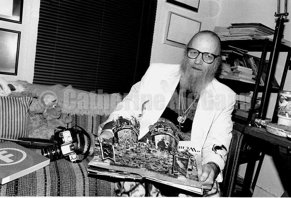 """January 1997:  A portrait of artist and photographer Billy Name at home in Poughkeepsie, New York, holding a copy of the """"Andy Warhol Index Book""""."""