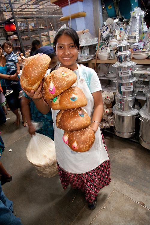 """North America, Mexico, Oaxaca Province, Ocotlan, teenage girl with special bread (""""'pan de muertos"""")  for sale during annual Day of the Dead (Dias de los Muertos) celebration in November"""