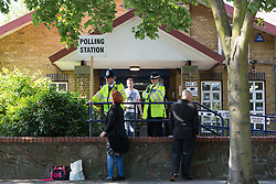© Licensed to London News Pictures. 11/06/2015. London, UK. Police chat to canvassers outside a polling station in Stepney, Tower Hamlets, east London. Tower Hamlets residents go to the polls today to vote for a new Mayor of Tower Hamlets after Lutfur Rahman was removed from office for fraud in corrupt practices by an election court earlier this year. Photo credit : Vickie Flores/LNP