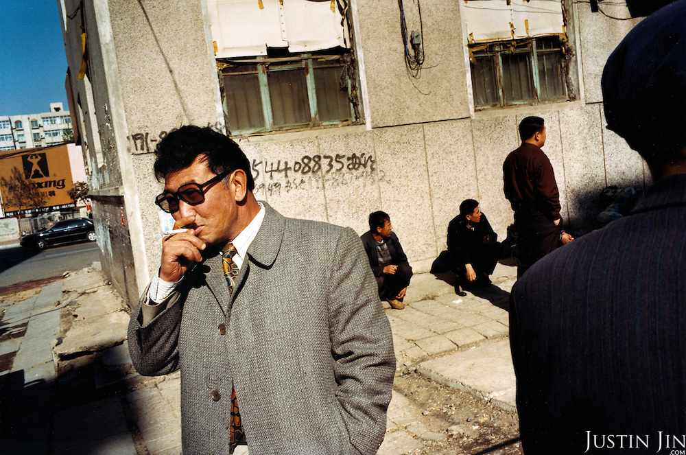 Men hang about in Tieling City, in China's northeastern rustbelt. .Millions of workers have been laid-off as China restructures its economy, making way for nimble manufacturing bases down south. Thousands of unemployed workers from Tieling have fled to Europe as clandestine immigrants..Picture taken by Justin Jin in Tieling city, Liaoning Province, China, 11-2003
