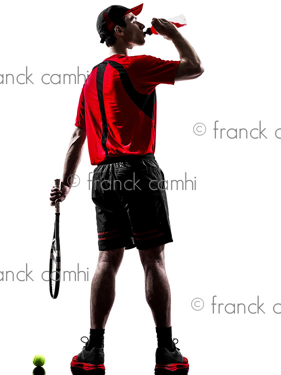 one young man tennis player drinking energy drinks in silhouette isolated on white background