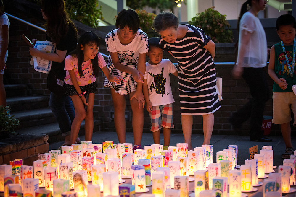 NAGASAKI, JAPAN - AUGUST 8 : People look at candle-lit paper lanterns with written message at Nagasaki Peace Park on the eve ahead of the 71st anniversary activities, commemorating the atomic bombing of Nagasaki on August 8, 2016 in Nagasaki, southern Japan. On August 9, 1945, during World War II, the United States dropped the second Atomic bomb, a plutonium implosion-type bomb on Nagasaki city, killing an estimated 40,000 people which ended the World War II. (Photo by Richard Atrero de Guzman/NURPhoto)
