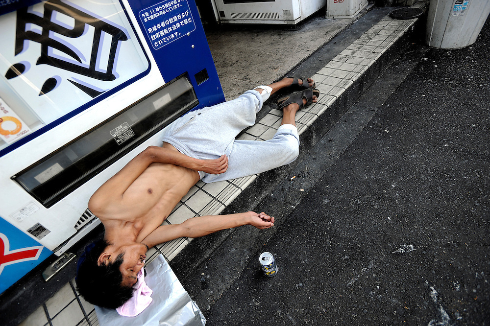 "A man lies unconscious outside a booth containing several  automatic vending machines selling alcoholic  drinks in the Kamagasaki district of Osaka, Japan on July 23 2008. Alcoholism afflicts a sizable portion of the city's homeless, with drinks machines such as those shown in this picture selling almost entirely low-priced beers and ""sake"", a wine-like beverage fermented from rice. What's more, tuberculosis sufferers in Kamagasaki number 30 to 40 times the national average."