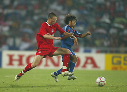 BANGKOK, THAILAND - Thailand. Thursday, July 24, 2003: Liverpool's Anthony Le Tallec and Thailand's Issawa Singthong during a preseason friendly match at the Rajamangala National Stadium. (Pic by David Rawcliffe/Propaganda)