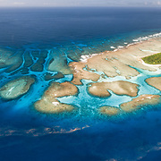 This is an aerial panorama of Maninita Island in the Vava'u island group of the Kingdom of Tonga. The island sits atop an extensive coral reef structure, which is for the most part not visible from the surface of the ocean. The reefs extend into the background, reaching the smaller island of Fonuafo'ou. This photograph was taken a few days before the full moon. The pinkish-red threads visible on the ocean surface are billions of gametes, perhaps spawned from the coral around Manninita and other nearby reefs.