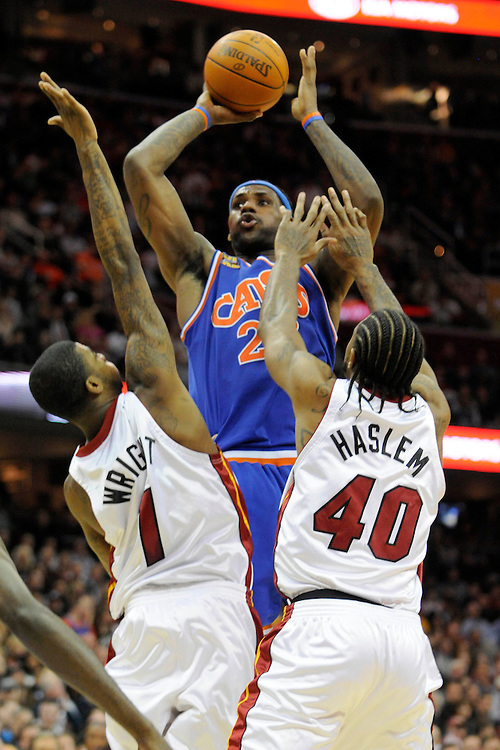 Feb 4, 2010; Cleveland, OH, USA; Cleveland Cavaliers forward LeBron James (23) shoots over Miami Heat forward Dorell Wright (1) and Miami Heat forward Udonis Haslem (40) during the fourth quarter at Quicken Loans Arena. The Cavaliers beat the Heat 102-86. Mandatory Credit: Jason Miller-US PRESSWIRE