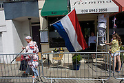 Dutch cycling fan walks past Italian restaurant on the first day of competition of the London 2012 Olympic 250km mens' road race. Starting from central London and passing the capital's famous landmarks before heading out into rural England to the gruelling Box Hill in the county of Surrey. Local southwest Londoners lined the route hoping for British favourite Mark Cavendish to win Team GB first medal but were eventually disappointed when Kazakhstan's Alexandre Vinokourov eventually won gold.