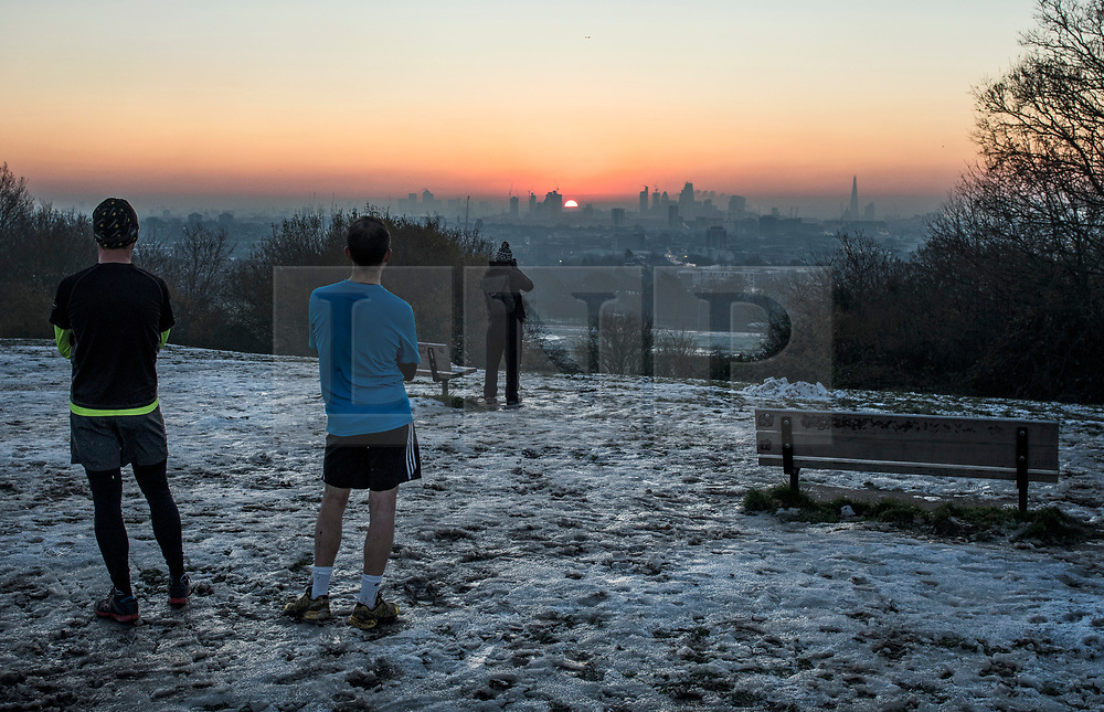 © Licensed to London News Pictures. 12/12/2017. London, UK. Jogger stop to watch the sun rise over the city of London from Hampstead Heath on a freezing morning. Temperatures across the the UK dipped overnight with some regions expected to drop to -13C (9F). Photo credit: Ben Cawthra/LNP