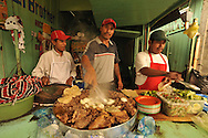 Food vendors in their street stalls preparing breakfast for farm laborers in Ixcan, Guatemala - a dusty border town near Mexico.