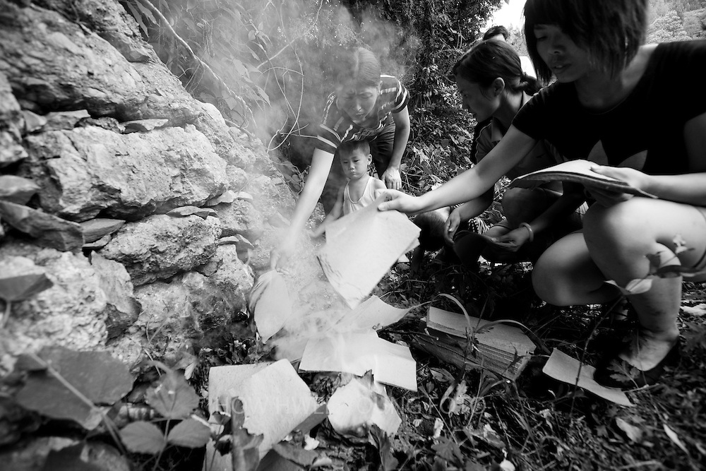Villagers of Cangfang town burn paper money in their last visit to the ancestral tomb before relocation to neighbouring Hui county to make way for the colossal South-to-North Water Transfer project in Xichuan county of Henan Province in China on 28 June 2010. The central route, which will raise the height of the Danjiangkou reservoir dam from 162 meters to 176.6 meters, requires the relocation of 330,000 people in Henan and Hubei provinces. Xichuan, a remote, mountainous region inaccessible by railway, is home to 162,000 would-be SNWD migrants, the most anywhere. The South-to-North Water Transfer project, the largest known water diversion project, was conceived in 1952 to solve the country's chronic water shortages and involves creating three routes to channel 44.8 billion cu m of water from southern China to the northern areas. As part of the project's central route, affecting Henan and Hubei provinces, water from the Danjiangkou reservoir will be diverted to Beijing. Parts of Xichuan county, a remote, mountainous region inaccessible by railway and home to 162,000 migrants, the most anywhere, will be completely submerged by water from the Danjiangkou reservoir by 2014. The vast resettlement of affected residents in Xichuan county began in August 2009 and lasted till 2011.