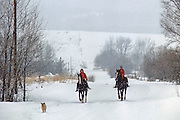 Two youngsters on horseback in snowstorm, Teton Valley, Idaho.