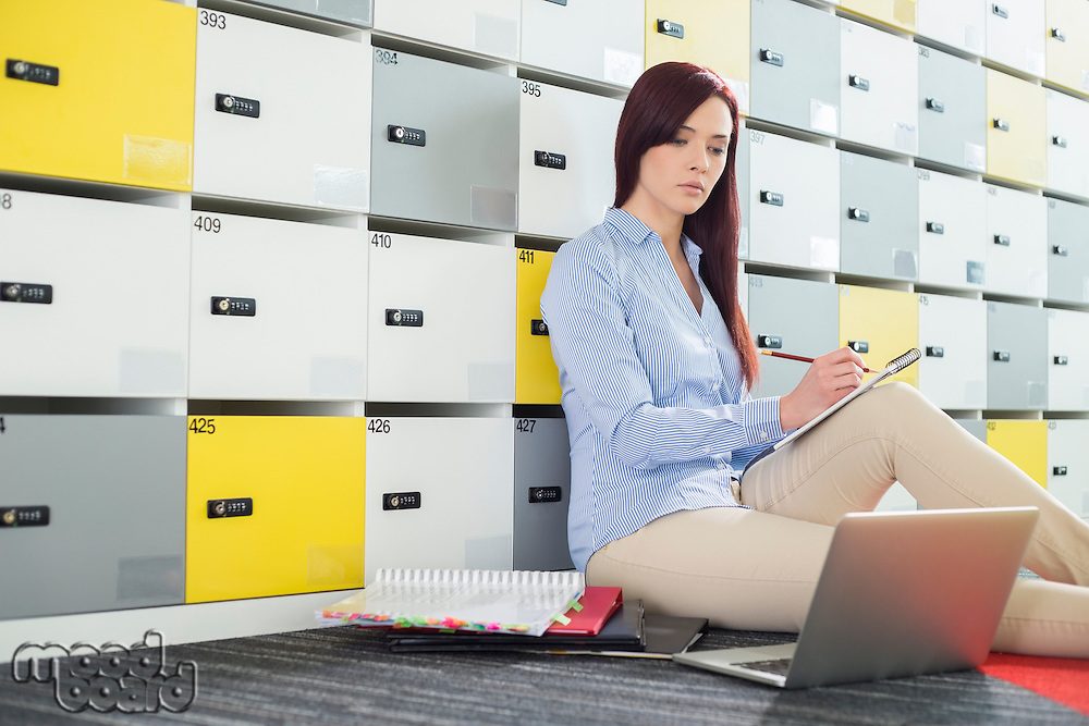 Beautiful businesswoman using laptop while writing in locker room at creative office