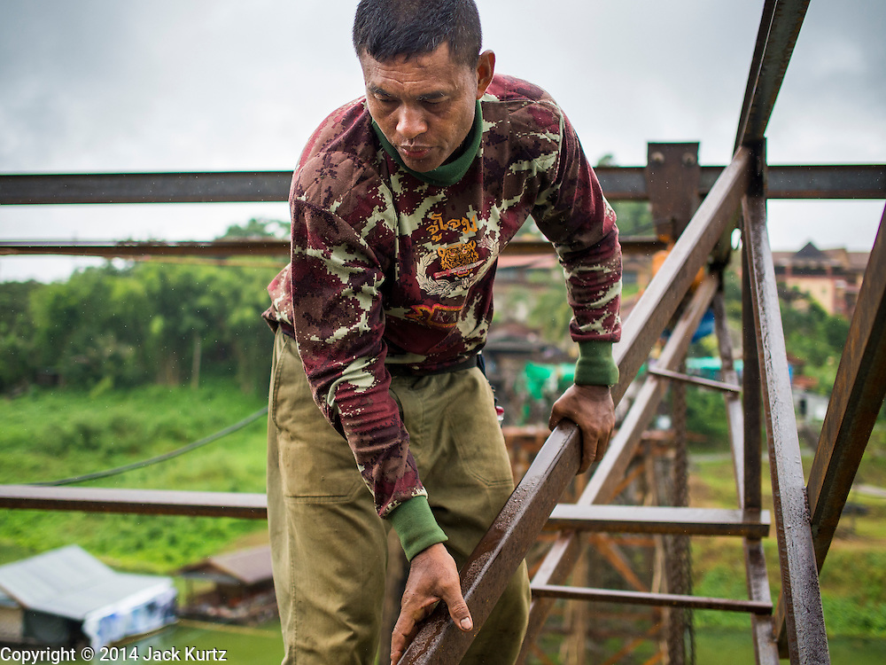 17 SEPTEMBER 2014 - SANGKHLA BURI, KANCHANABURI, THAILAND: A member of the Burmese Mon community in Sangkhla Buri works on the repair of the Mon Bridge. The 2800 foot long (850 meters) Saphan Mon (Mon Bridge) spans the Song Kalia River. It is reportedly second longest wooden bridge in the world. The bridge was severely damaged during heavy rainfall in July 2013 when its 230 foot middle section  (70 meters) collapsed during flooding. Officially known as Uttamanusorn Bridge, the bridge has been used by people in Sangkhla Buri (also known as Sangkhlaburi) for 20 years. The bridge was was conceived by Luang Pho Uttama, the late abbot of of Wat Wang Wiwekaram, and was built by hand by Mon refugees from Myanmar (then Burma). The wooden bridge is one of the leading tourist attractions in Kanchanaburi province. The loss of the bridge has hurt the economy of the Mon community opposite Sangkhla Buri. The repair has taken far longer than expected. Thai Prime Minister General Prayuth Chan-ocha ordered an engineer unit of the Royal Thai Army to help the local Mon population repair the bridge. Local people said they hope the bridge is repaired by the end November, which is when the tourist season starts.    PHOTO BY JACK KURTZ