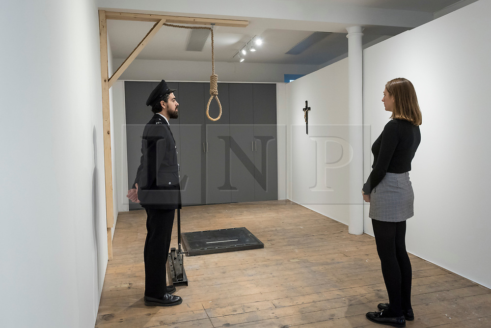 """© Licensed to London News Pictures. 13/11/2018. LONDON, UK. Staff members, one posing as a prison guard, view a hangman's noose.  Preview of """"Glad I Did It"""", a new work by Irish artist Christina Reihill at Bermondsey Project Space.  The interactive artwork looks at the life and death of Ruth Ellis, the last woman to be hanged in Britain, after she shot her lover, racing driver, David Blakely in 1955.  On display are the artist's interpretation of Ruth Ellis' prison cell, including furniture and props, the hanging room together with a video display of the artist in conversation.   The show runs 14 November to 1 December 2018.  Photo credit: Stephen Chung/LNP"""
