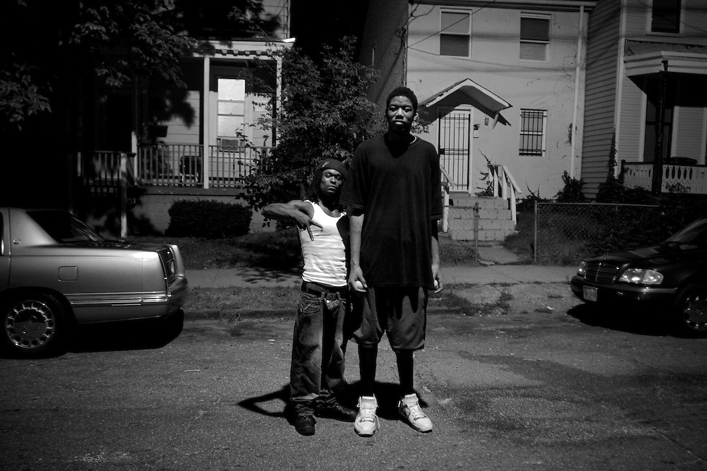 """Hassan (left) works as a brick layer, but sells pirated and pornographic movies on the street to make ends meet for his two daughters. He stopped to take this photograph with a passing basketball player (right) whose height caught his attention. When asked what he thought about the neighborhood the player, who is new to Anacostia responded, """"it's not as bad as everybody says."""""""