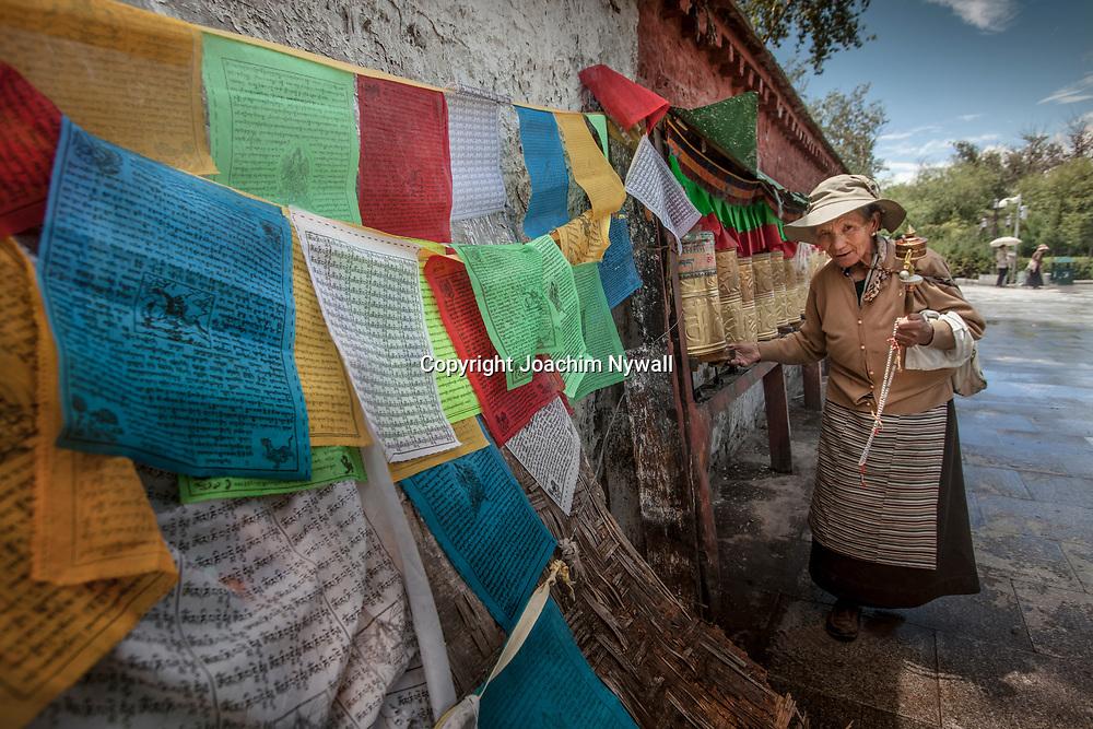Lhasa 2011 Tibet<br /> Gammal kvinna med b&ouml;nesnurra g&aring;r runt Potalapalatset i Lhasa<br /> B&ouml;neflaggor<br /> ----<br /> FOTO : JOACHIM NYWALL KOD 0708840825_1<br /> COPYRIGHT JOACHIM NYWALL<br /> <br /> ***BETALBILD***<br /> Redovisas till <br /> NYWALL MEDIA AB<br /> Strandgatan 30<br /> 461 31 Trollh&auml;ttan<br /> Prislista enl BLF , om inget annat avtalas.