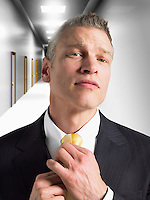 Man adjusting tie in corridor head and shoulders