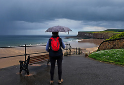 © Licensed to London News Pictures. 19/05/15<br /> <br /> Saltburn, UK. <br /> <br /> A woman stands and looks towards Huntcliff as heavy storm clouds gather over Saltburn by the Sea in Cleveland.<br /> <br /> Photo credit : Ian Forsyth/LNP