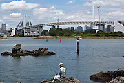 Men fishing in Odaiba with a view of the Rainbow Bridge and Tokyo city-scape