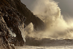 © Licensed to London News Pictures. 29/01/2016. Criccieth, Gwynedd, Wales, UK. Huge waves crash against a breakwater against hgh cliff faces. Gale force winds batter the North Wales seaside resort of Criccieth in Gwynedd, Wales, last night and this morning. Photo credit: Graham M. Lawrence/LNP