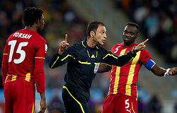 Isaac Vorsah of Ghana and John Mensah of Ghana with a referee Olegario Benquerenca (POR) during the  2010 FIFA World Cup South Africa Quarter Finals football match between Uruguay and Ghana on July 02, 2010 at Soccer City Stadium in Sowetto, suburb of Johannesburg. Uruguay defeated Ghana after penalty shots. (Photo by Vid Ponikvar / Sportida)