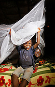 Brothers play under their new mosquito net in the Nyarugusu Refugee Camp in Tanzania, during a Nothing But Nets trip to distribute anti-malaria bed nets, Tuesday, July 30, 2013. (Insider Images/Stuart Ramson for UN Foundation)