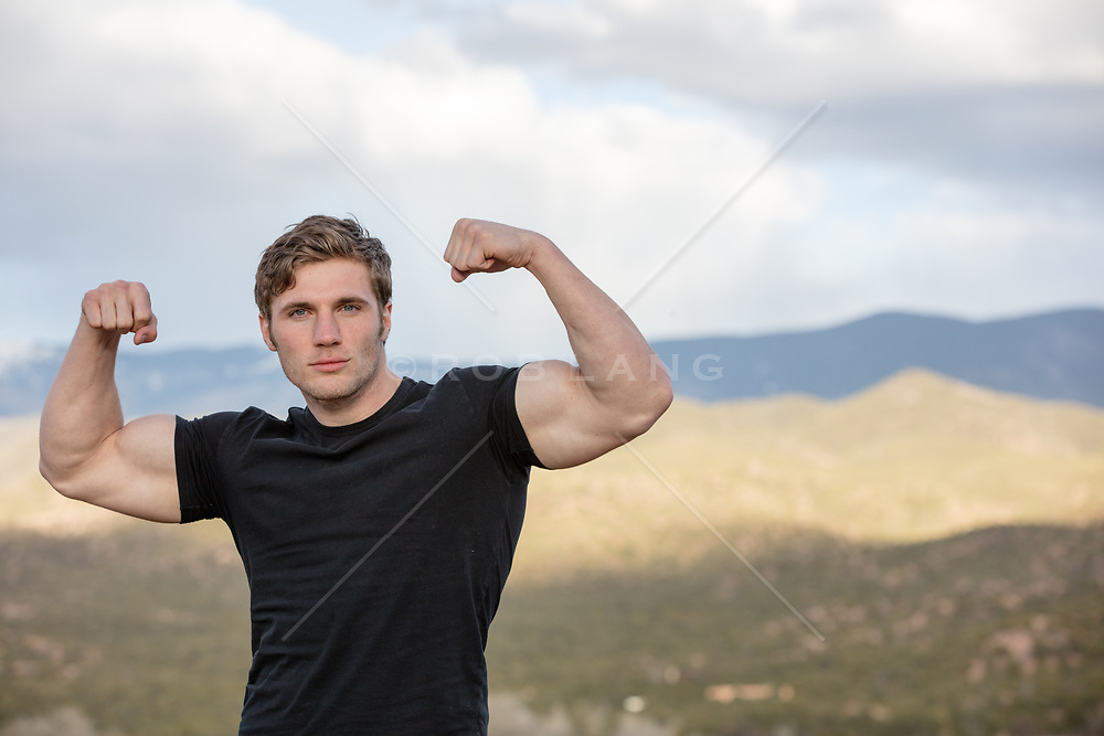 man making a muscle pose outdoors by a mountain range