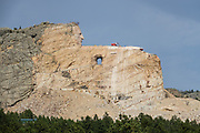 The Crazy Horse Memorial is being carved into Thunderhead Mountain on private land in the Black Hills, between Custer and Hill City, 17 miles from Mount Rushmore, in Custer County, South Dakota, USA. In progress since 1948, the sculpture is far from completion. It depicts the Oglala Lakota warrior, Crazy Horse, riding a horse and pointing into the distance. The memorial was commissioned by Henry Standing Bear, a Lakota elder, to be sculpted by Korczak Ziolkowski. It is operated by the nonprofit Crazy Horse Memorial Foundation. The sculpture is planned to be of record-setting size: 641 feet wide and 563 feet high. The head of Crazy Horse will be 87 feet high (whereas the heads of the four U.S. Presidents at Mount Rushmore are each 60 feet high). Crazy Horse (1840–1877) was a Native American war leader of the Oglala Lakota. He took up arms against the United States federal government to fight against encroachment by white American settlers on Indian territory. He earned great respect from both his enemies and his own people in several battles of the American Indian Wars on the northern Great Plains, including: the Fetterman massacre in 1866, in which he acted as a decoy, and the Battle of the Little Bighorn in 1876, in which he led a war party to victory. Four months after surrendering in 1877, Crazy Horse was fatally wounded by a bayonet-wielding military guard, while allegedly resisting imprisonment at Camp Robinson in present-day Nebraska. In 1982 he was honored by the U.S. Postal Service with a 13¢ Great Americans series postage stamp.