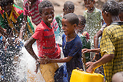Tartuarwa, Ethiopia - 17.05.16  - Students react as a water hose breaks loose at Tartuarwa primary school in the district of East Belessa, Ethiopia on May 17, 2016. Students -- and impaired community members -- receive a daily meal and water thanks to a CBM-funded inclusive school feeding and water distribution program. The water itself is funded by German Agro Action (Deutsche Welthungerhilfe). Photo by Daniel Hayduk