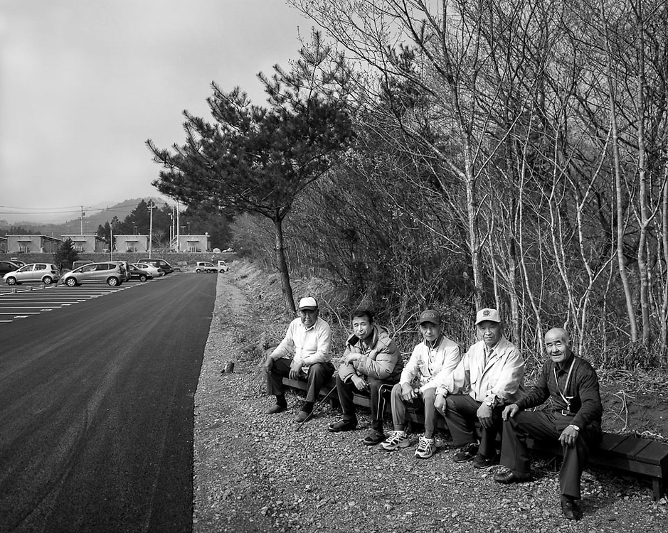 Mr. Megro  83 (right) sitting with some of his  neighbors all from the  village of Iitate, Fukushima  in the parking lot of their temporary  housing in Soma  more then 30km from his contaminated farm in iitate. unable to farm he is forced to evacuate his farm in order to receive assistance.