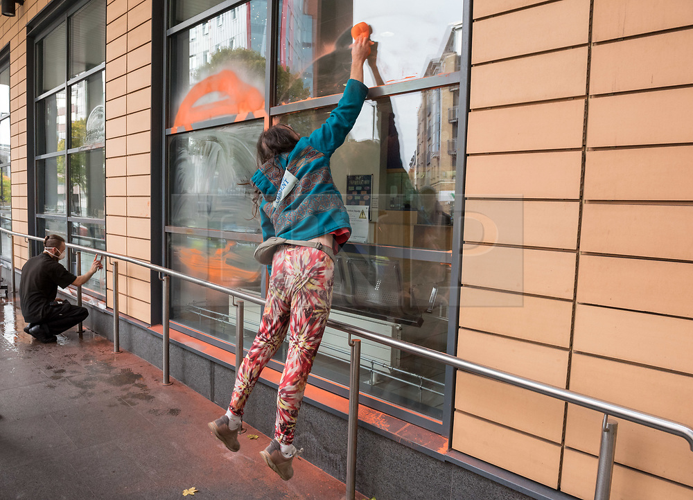 © Licensed to London News Pictures. 08/10/2018. Bristol, UK. A campaigner removes chalk spray from the window of Bristol Magistrates Court after the 'Extinction Rebellion' campaign event 'Make Ecocide Law' about the threat of climate change, at Bristol Magistrates Court and Marlborough Street. The campaign wants to make ecocide a crime in UK law, saying the threat of climate change threatens the lives of millions of people on the planet. The campaign is organised by Rising Up, and the event happened on the day that the Intergovernmental Panel on Climate Change (IPCC) has issued a special report on the impact of global warming of 1.5C. Campaigners used removable chalk spray to write on the windows of Bristol Magistrates Court, and blocked the main road before being removed by police. There were three arrests. Rising Up plans more actions in November. Photo credit: Simon Chapman/LNP