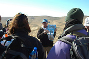 Israel, Negev plains, A guide explaining the zoology of the local snails to a group hiking on the mountain