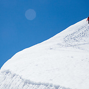 Chris Kitchen, Griffin Post, and Lynsey Dyer hike up a cornice line in Glacier National Park.