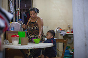 Rosmery gives her grandson breakfast in their home,  São Paulo , Brazil.<br /> <br /> Rosmery is Bolivian and moved to Brazil in search of work. Prior to moving in to her own home she lived and worked in a sewing workshop with her family, often for up to 16 hours a day. <br /> <br /> Nowadays she still sews and has long days, but she is based from home.<br /> <br /> Rosmery has received a lot of help and support from Missao Paz who work in partnership with C&A Foundation to  offer advice and support on employment, health, family, community and education.
