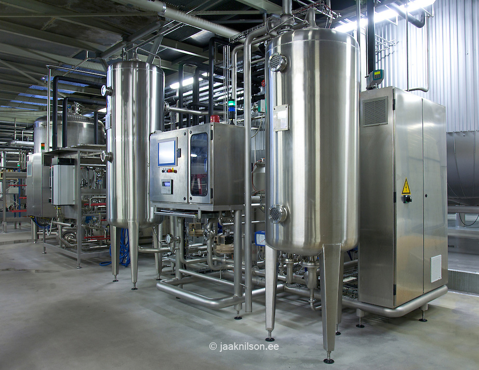 Beer brewing process, production plant. Large storage and fermenting tanks. Stainless steel. Pipework network.