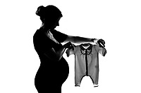 one beautiful caucasian pregnant woman holding baby clothes in silhouette on studio isolated white background