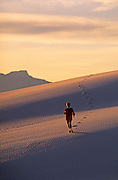 Image of a woman running on the dunes at White Sands National Monument in New Mexico, American Southwest, model released