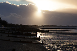 © Licensed to London News Pictures. 01/02/2014. Titchfield, Hampshire, UK. Sunrise near Titchfield Haven in Hampshire as a storm clouds pass in the distance. There is wet and windy weather forecast for the UK today, 1st February 2014. Photo credit : Rob Arnold/LNP