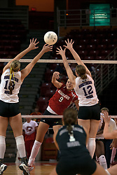25 September 2004   Emily Kabbes pounds it past Danielle Brazda (18) and Shari Vermeer (12).  Libero Stephanie May gets ready.      Illinois State University Redbirds V University of Northern Iowa Panthers Volleyball.  Redbird Arena, Illinois State University, Normal IL