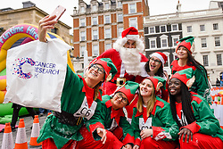 © Licensed to London News Pictures. 08/12/2018. LONDON, UK.  Competitors take a selfie during The 38th Great Christmas Pudding Race in Covent Garden, raising funds for Cancer Research as well as having a lot of festive fun.  Photo credit: Stephen Chung/LNP
