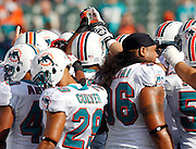 Miami Dolphins players huddle and join hands before the NFL week 8 football game against the Cincinnati Bengals on Sunday, October 31, 2010 in Cincinnati, Ohio. The Dolphins won the game 22-14. (©Paul Anthony Spinelli)